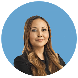 A headshot of Emilie Choi, Coinbase COO and President, smiling in a black blazer