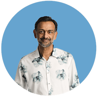 A headshot of Paul Grewal, Coinbase CLO, smiling in a floral button-up